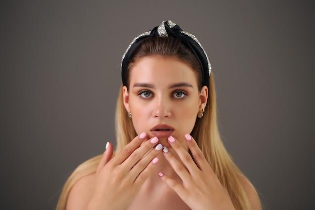 Attraktive junge frau, die ihre lippen berührt.