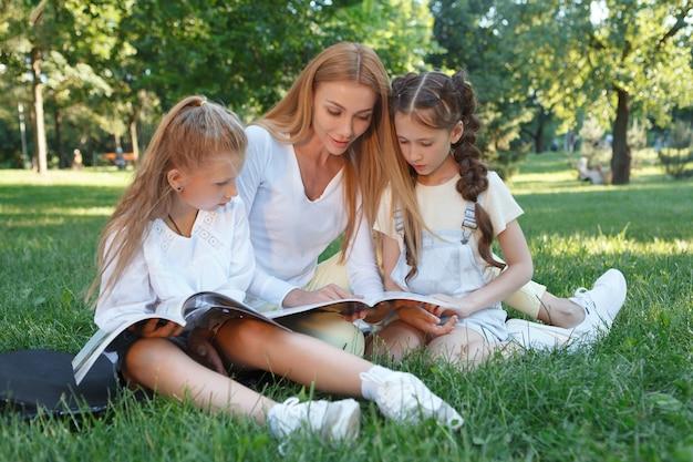 Attraktive junge frau, die ihren schülern ein buch vorliest und im gras sitzt