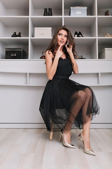 Attraktive junge frau, die im ankleidezimmer mit nachdenklichem blick sitzt und per telefon spricht. sie hat langes braunes lockiges haar, trägt ein schönes schwarzes kleid und silberne schuhe.