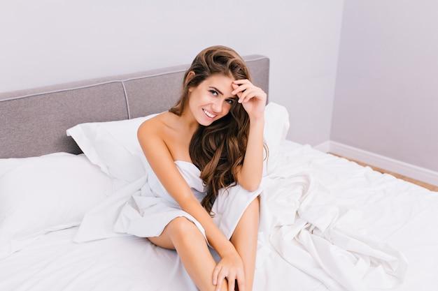 Attraktive junge frau, die im bett in der modernen wohnung kühlt. freudiges erstaunliches lächelndes mädchen mit langen brünetten haaren, die zu hause entspannen. aufwachen, positive wahre gefühle, guten morgen, süßes schönes modell.