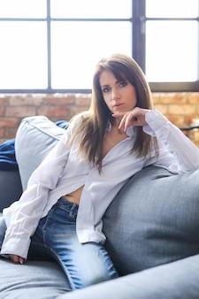 Attraktive junge frau, die im hemd und in den jeans aufwirft