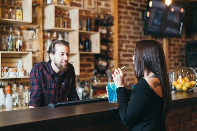 Attraktive junge frau, die im nachtclub sitzt, blauen lagunencocktail trinkt und mit barkeeper spricht. selektiver fokus auf frau.