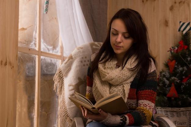Attraktive junge frau, die im winter neben einer mattierten holzfensterscheibe liest