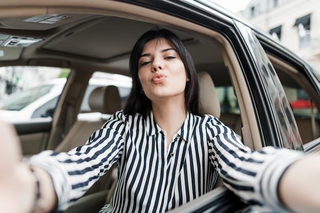 Attraktive junge frau, die in einem auto macht ein selfie an ihrem telefon sitzt