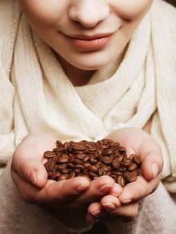 Attraktive junge frau, die kaffeebohnen hält.