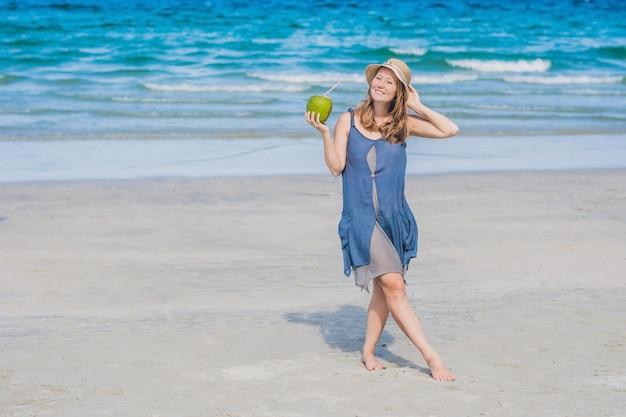 Attraktive junge frau, die kokosnusswasser am strand trinkt.
