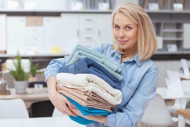 Attraktive junge frau, die lächelt und stapel neuer handtücher trägt, einkaufen im einrichtungsgeschäft
