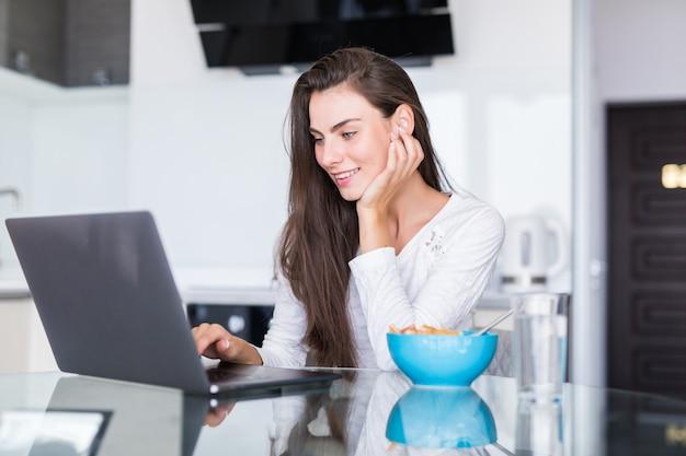 Attraktive junge frau, die laptop beim frühstück benutzt und in der küche sitzt.