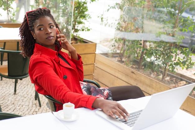 Attraktive junge frau, die laptop und smartphone im restaurant verwendet