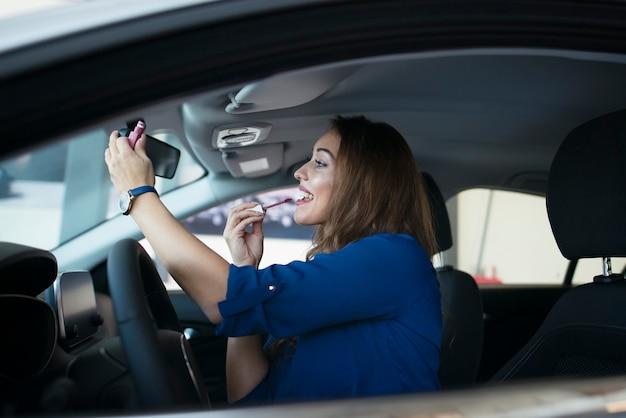 Attraktive junge frau, die lippenstift in einem auto aufsetzt