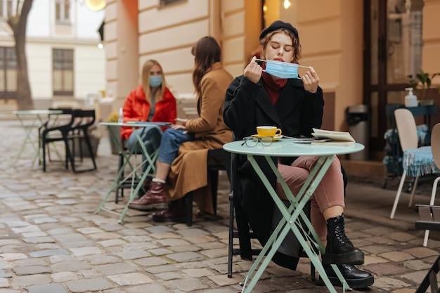 Attraktive junge frau, die medizinische maske für das trinken des heißen kaffees im örtlichen café abnimmt.