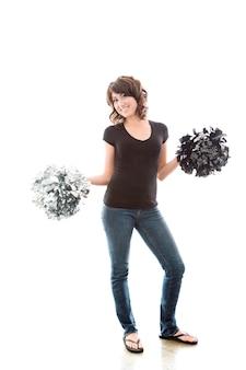 Attraktive junge frau, die mit cheerleader pom-poms aufwirft