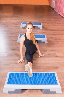 Attraktive junge frau, die mit füßen auf den fitnessplattformen in die luft spuckt und in die kamera schaut.