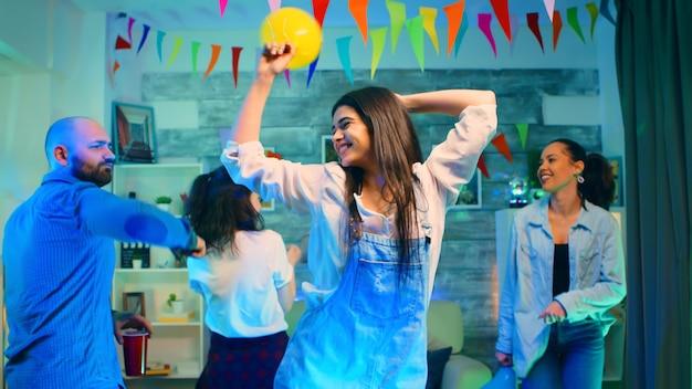 Attraktive junge frau, die mit ihren freunden feiert, während sie einen ballon hält. wilde college-party mit einem raum voller neonlichter, discokugel und alkohol