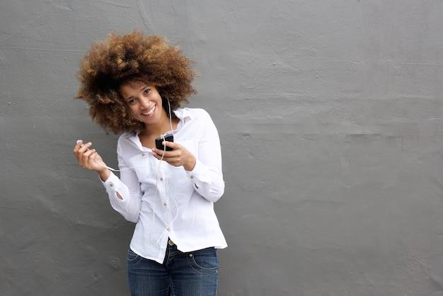 Attraktive junge frau, die mit kopfhörern und intelligentem telefon lächelt