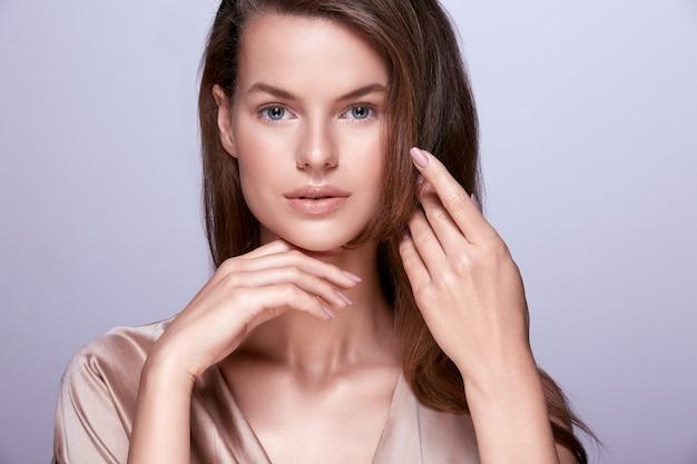 Attraktive junge frau, die nacktes make-up mit perfekter haut und langen haaren trägt, die am studiohintergrund aufwerfen.
