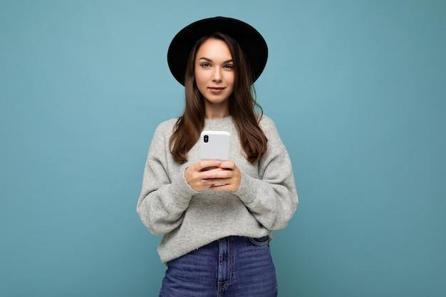 Attraktive junge frau, die schwarzen hut und grauen pullover hält, der smartphone betrachtet kamera lokalisiert