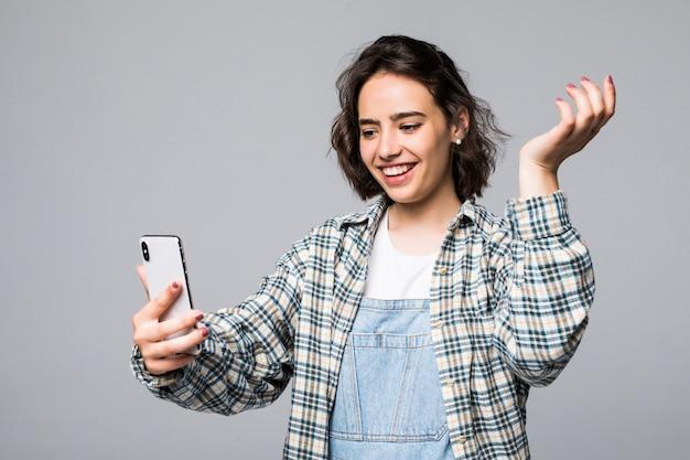 Attraktive junge frau, die selfie mit telefon nimmt