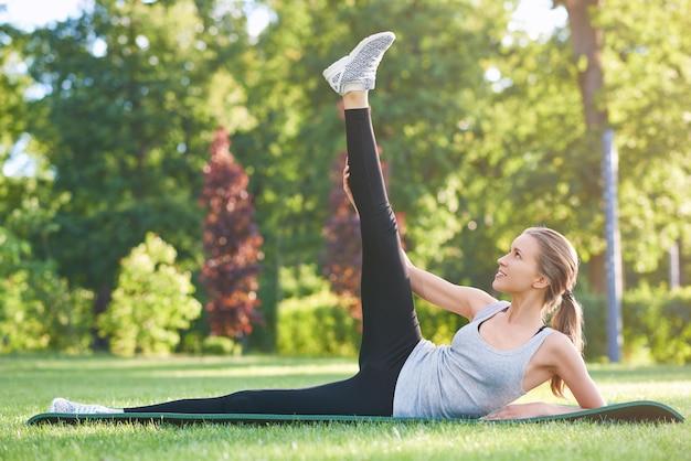 Attraktive junge frau, die sich am park ausdehnt, der im freien glück vitalität positivität flexibilität gymnastik aktiven lebensstil fitness gesundheitskonzept trainiert.