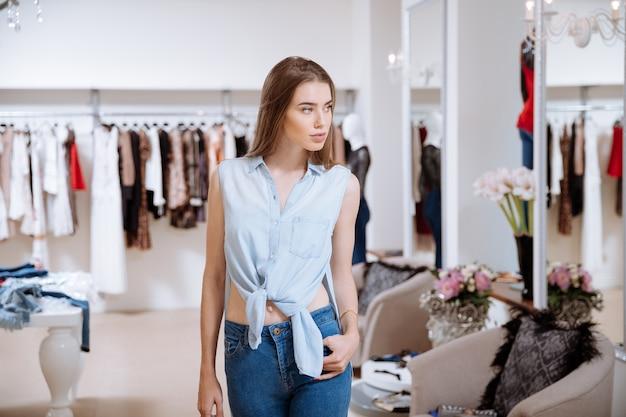Attraktive junge frau, die spazieren geht und im kleidergeschäft einkauft