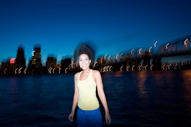 Attraktive junge frau, die städtische ufergegend bei sonnenuntergang bereitsteht