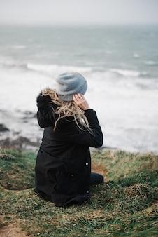 Attraktive junge frau, die tagsüber auf einer klippe am schönen meer sitzt