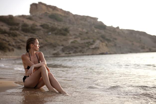 Attraktive junge frau, die tagsüber den schönen blick auf das friedliche meer am strand genießt