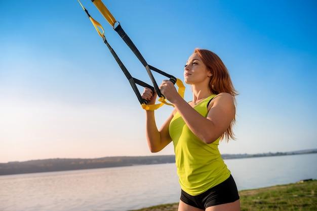 Attraktive junge frau, die tagsüber trx-training im freien nahe dem see tut. gesunder lebensstil
