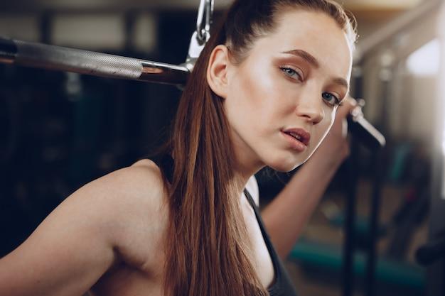 Attraktive junge frau, die übungen für die muskeln der arme und zurück in einem fitnessstudio macht