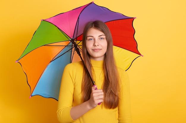 Attraktive junge frau, die unter mehrfarbigem regenschirm steht und gelben pullover trägt