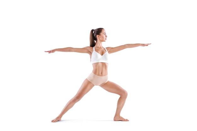 Attraktive junge frau, die yogaübung virabhadrasana tut, lokalisiert auf weißem hintergrund. kontrollieren sie das gleichgewicht, studio in voller länge.