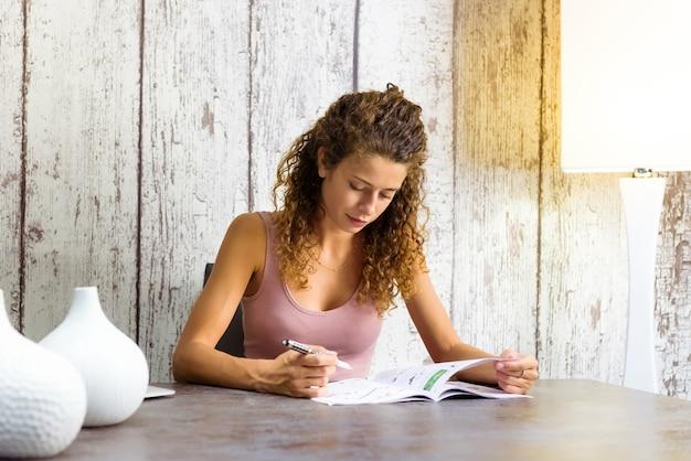 Attraktive junge frau, die zu hause an kreuzworträtseln in einer zeitschrift arbeitet, die an einem tisch mit copyspace sitzt