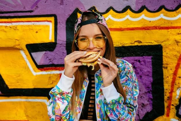 Attraktive junge frau, einen geschmackvollen burger essend. in bunte jacke und mütze gekleidet