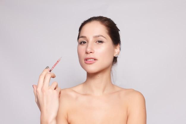 Attraktive junge frau erhält kosmetische injektion, isoliert über weißem hintergrund. weibliche hand hält eine spritze zur injektion in der nähe des gesichts. schönheitsbehandlung.
