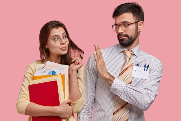 Attraktive junge frau flirtet mit gutaussehendem männlichen kollegen, trägt bücher und dokumente