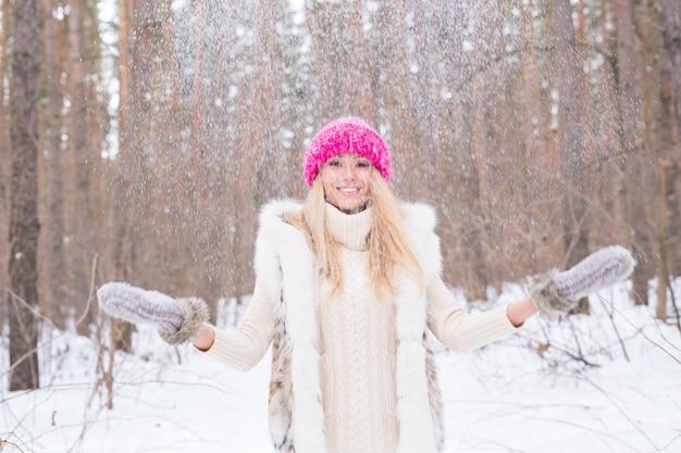 Attraktive junge frau gekleidet im mantel, der schnee wirft.
