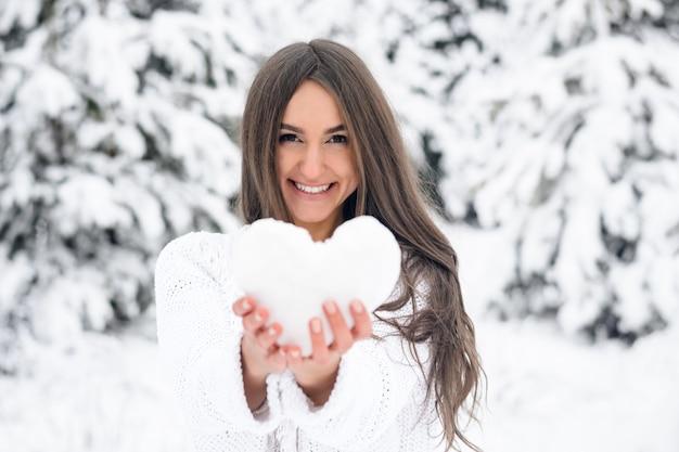 Attraktive junge frau hält ein herz vom schnee im winterwald im winterwald