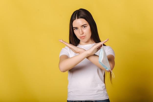 Attraktive junge frau halten schutzmaske in der hand und denken an die notwendigkeit weiblicher kreuzarme