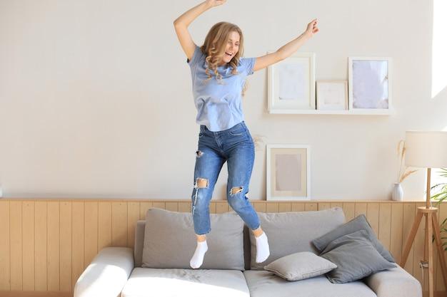 Attraktive junge frau hat spaß zu hause. mädchen springt und tanzt auf dem sofa.