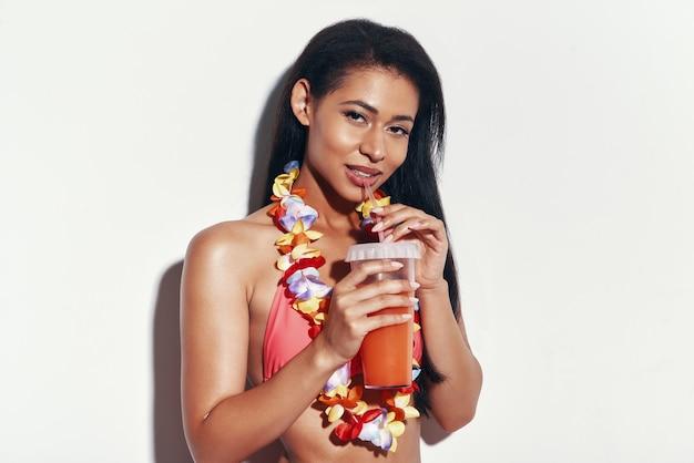 Attraktive junge frau im bikini, die erfrischenden cocktail trinkt und lächelt, während sie vor grauem hintergrund steht