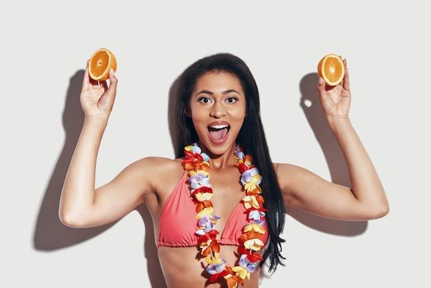 Attraktive junge frau im bikini, die kamera anschaut und lächelt, während sie vor grauem hintergrund steht