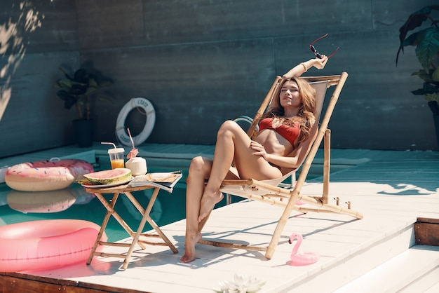 Attraktive junge frau im bikini, die sich beim sonnenbaden am pool im freien entspannt und lächelt