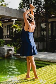 Attraktive junge frau im blauen kleid und im strohhut am pool