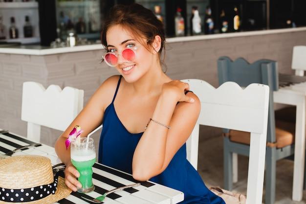 Attraktive junge frau im blauen kleid und im strohhut, die rosa sonnenbrille trägt, alkoholcocktails im tropischen urlaub trinkt und am tisch in der bar sitzt
