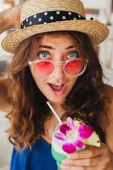 Attraktive junge frau im blauen kleid und im strohhut, die rosa sonnenbrille trinkende alkoholcocktails im tropischen urlaub sitzen am tisch in der bar im sommerart-outfit sitzen und glücklich in der party-stimmung lächeln