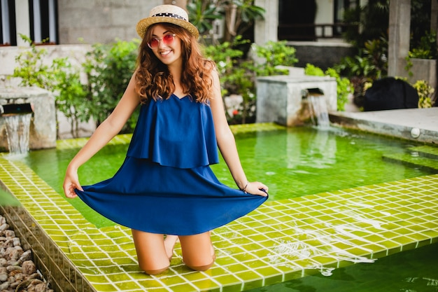 Attraktive junge frau im blauen kleid und im strohhut, die rosa sonnenbrillen am pool tragen