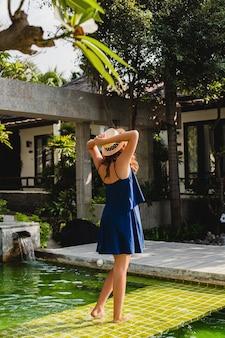 Attraktive junge frau im blauen kleid und im strohhut, die rosa sonnenbrillen tragen, die am pool der tropischen spa-villa im urlaub im sommerart-outfit gehen, ansicht vom rücken, der hände hoch hält