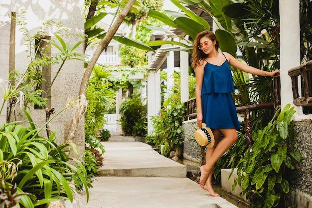 Attraktive junge frau im blauen kleid und im strohhut, die rosa sonnenbrillen tragen, die im tropischen spa-villenhotel im urlaub im sommerart-outfit sexy gehen