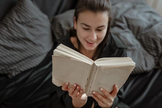 Attraktive junge frau im pyjama entspannt sich im bett beim lesen eines buches.