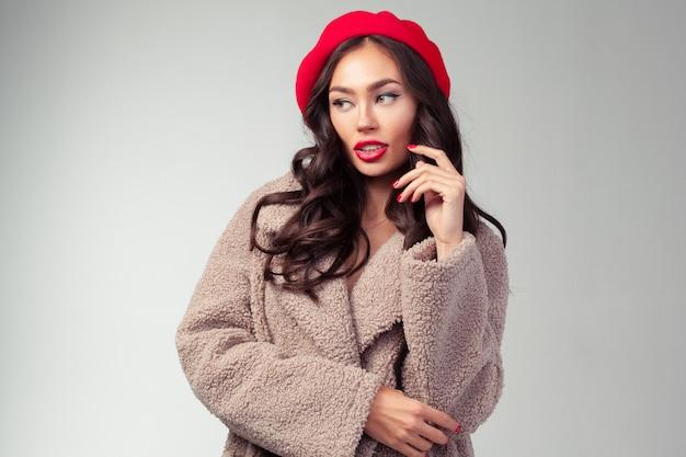 Attraktive junge frau im roten barett und im modernen mantel